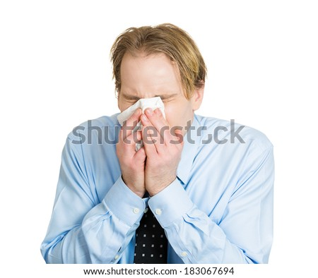 Closeup portrait of sick, ill young man, student, worker with allergy, germs cold, blowing his nose with kleenex, looking miserable, unwell, very sick isolated on white background. Flu season, vaccine - stock photo