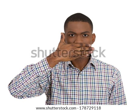 Closeup portrait of silent young man covering closed mouth observing. Speak no evil concept, isolated white background. Negative human emotions, facial expressions signs, symbols. Media news coverup