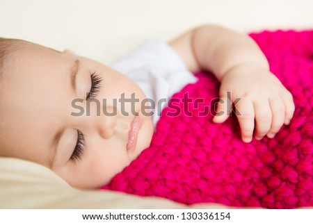 Closeup portrait of sleeping baby covered with knitted blanket - stock photo
