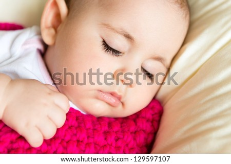 Closeup portrait of sleeping baby in pink knitted  blanket