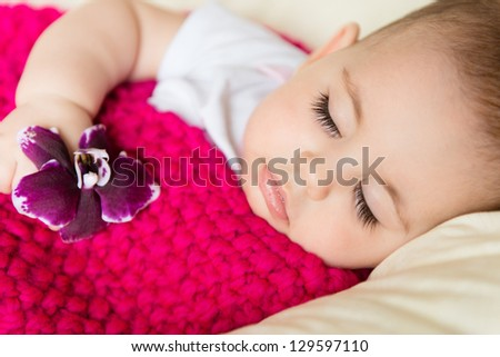 Closeup portrait of sleeping baby with flower in hand - stock photo