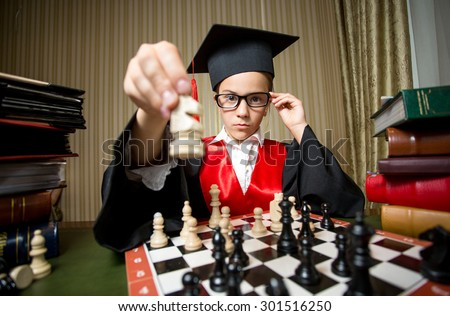 Closeup portrait of smart girl in graduation cap making move at chess with horse - stock photo