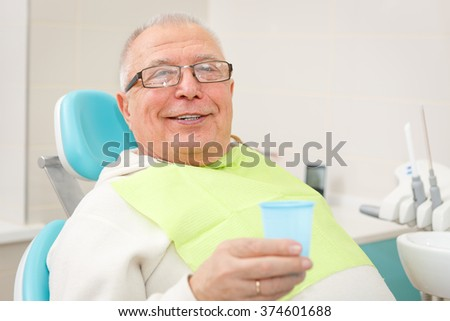 Closeup portrait of Smile Old senior man with plastic cup sitting in a chair in dental clinic. Looking to camera - stock photo