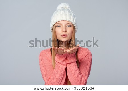 Closeup portrait of smiling beautiful blond female in pink sweater  blowing at palms, over white background - stock photo