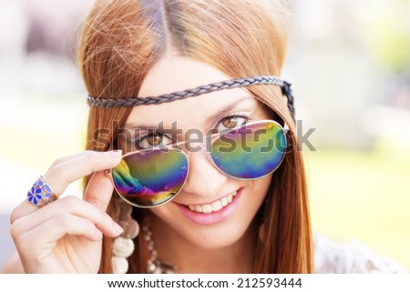 Closeup portrait of smiling beautiful hippie woman looking over sunglasses, outdoor.