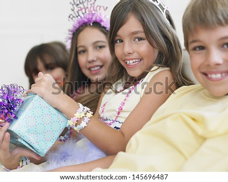 Closeup portrait of smiling children sitting in row at birthday party