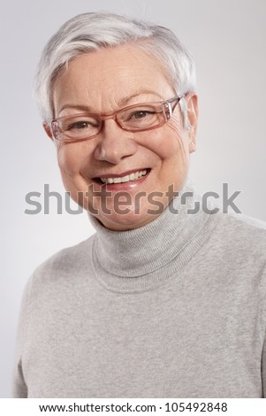 Closeup portrait of smiling elderly lady in grey sweater and glasses. - stock photo