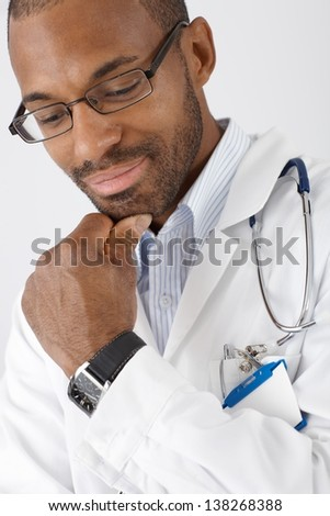 Closeup portrait of smiling ethnic doctor thinking cutout on white. - stock photo