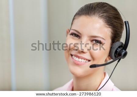 Closeup portrait of smiling female customer service representative wearing headset in call center - stock photo