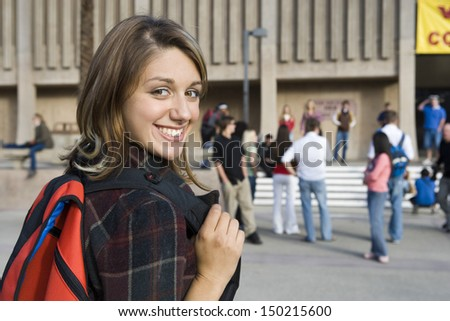 Closeup portrait of smiling female student on college campus with classmates in background