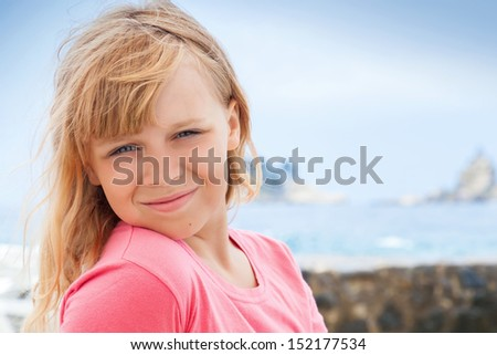 Closeup portrait of smiling little blond girl in pink on the seacoast - stock photo