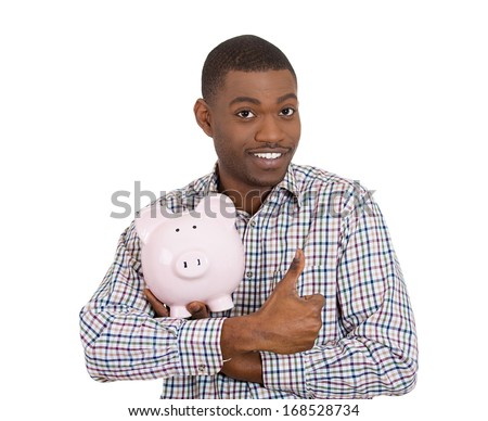 Closeup portrait of smiling man, student, young guy, worker holding piggy bank tightly trying, giving thumbs up, isolated on white background. Smart financial investment decisions. Budget management  - stock photo