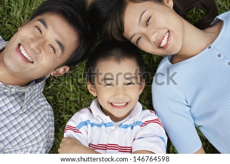 Closeup portrait of smiling parents with son lying on grass - stock photo