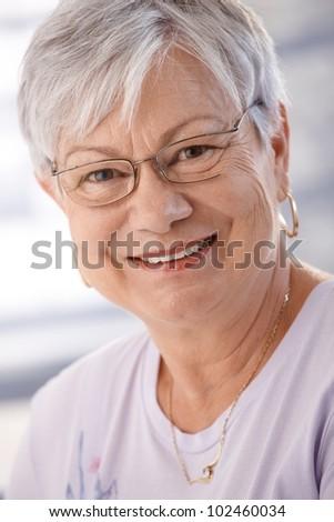 Closeup portrait of smiling senior lady, looking at camera. - stock photo