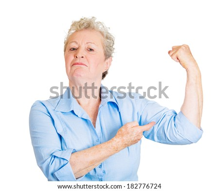 Closeup portrait of smiling senior mature woman flexing muscles showing displaying her gun show, isolated on white background. Positive emotion facial expression feelings, attitude, perception - stock photo