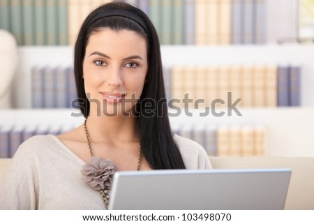 Closeup portrait of smiling woman with laptop computer at home, looking at camera. - stock photo