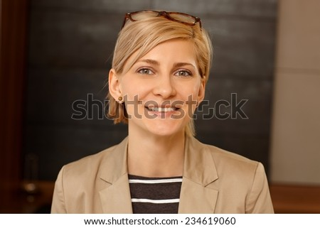 Closeup portrait of smiling young blonde woman looking at camera. - stock photo