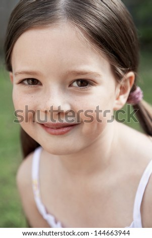 Closeup portrait of smiling young girl in park - stock photo