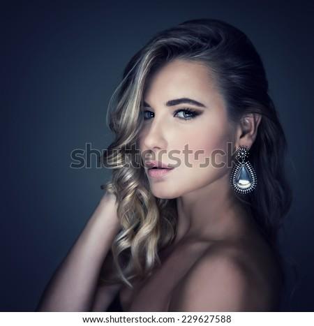 Closeup portrait of stunning woman isolated on dark gray background, sexual model wearing stylish jewelery, beauty salon concept - stock photo