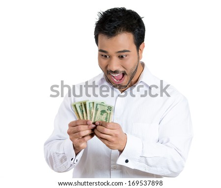 Closeup portrait of super happy excited successful young man holding money dollar bills in hand, isolated on white background. Positive emotion facial expression feeling. Financial reward savings - stock photo