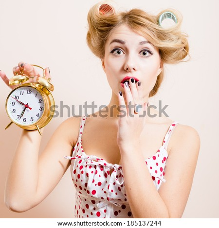 closeup portrait of surprised young beautiful green eyes woman attractive funny blond pinup girl holding golden alarm clock and looking at camera on light background - stock photo