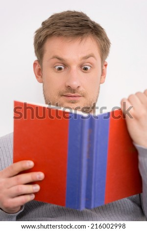 Closeup portrait of surprised young, handsome man reading book. man reading book sitting on sofa - stock photo