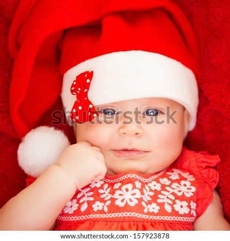 Closeup portrait of sweet little baby wearing Santa hat with stylish bow, red background, celebrating Christmas at home, joy and fun concept - stock photo