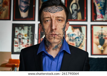 Closeup portrait of tattoo master in black jacked and blue shirt