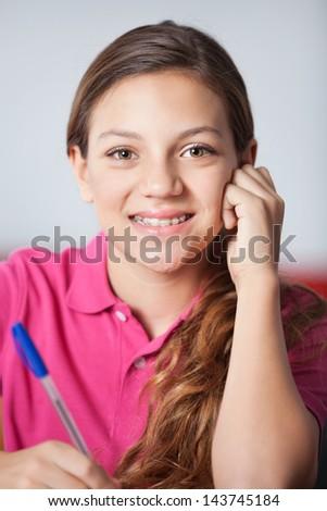 Closeup portrait of teenage schoolgirl in classroom - stock photo