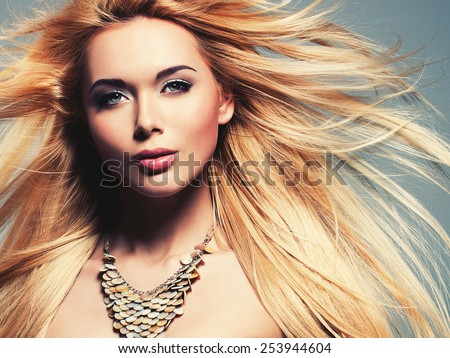 Closeup portrait of the beautiful sexy woman with long blonde hair. Fashion model posing in the studio on a black background with flying hair. - stock photo