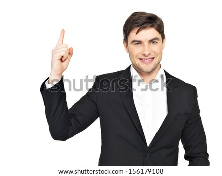Closeup portrait of the happy businessman points his finger up  in black suit isolated on white  - stock photo