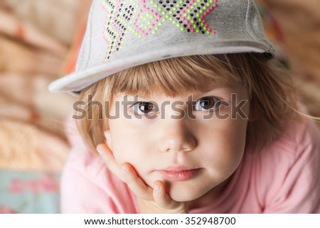 Closeup portrait of thinking cute Caucasian blond baby girl in gray cap
