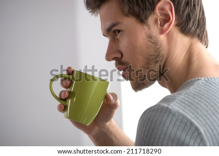 closeup portrait of thoughtful man having coffee. Handsome young man holding mug - stock photo
