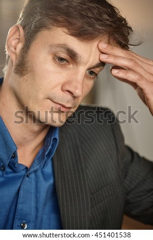 Closeup portrait of thoughtful troubled businessman thinking, hand on forehead, looking down. - stock photo