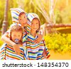 Closeup portrait of three funny child wearing same colorful clothing, beach towels, happy family hugging outdoors, summer holidays concept - stock photo