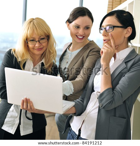 Closeup portrait of three women working indoor together with documents and laptop.