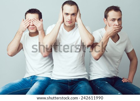Closeup portrait of three young men in white t-shirts imitating see no evil, hear no evil, speak no evil concept, isolated on gray background. Human emotions, expressions & communication. Studio shot