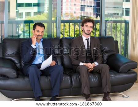 Closeup portrait of two bored businessman sitting on black couch applying and interviewing for a job, one guy has pen to mouth as mustache, other is daydreaming, isolated on a city urban background  - stock photo