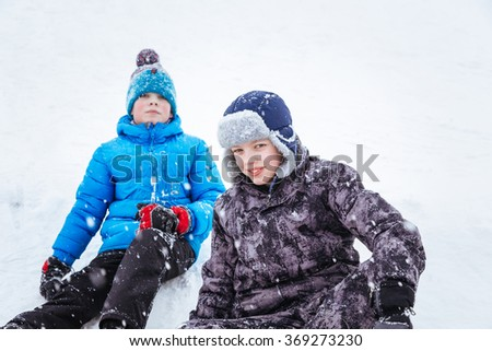 Closeup portrait of two boys, friends, sitting on snowy hill. Winter holidays concept.
