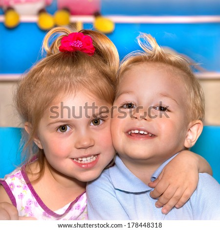 Closeup portrait of two cheerful child hugging each other, adorable siblings, smiling faces, best friends, love and friendship concept - stock photo