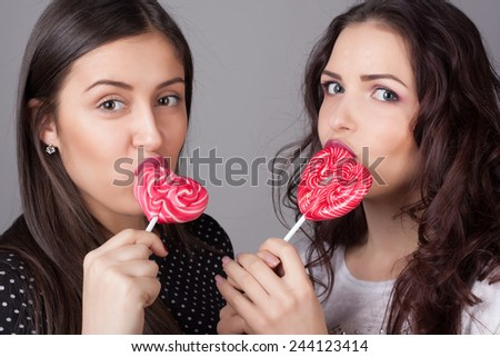 Closeup portrait of two girlfriend girls with lollipops. Happy and cheerful teens.