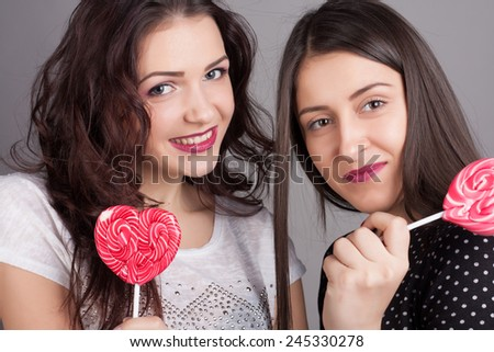 Closeup portrait of two girlfriend girls with lollipops. Happy and cheerful teens. - stock photo