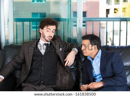 Closeup portrait of two guys in business suits sitting on black couch. One is crying about life problems and other probably caused the trouble or is indifferent. Human emotions and communication   - stock photo