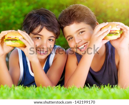 Closeup portrait of two happy baby boys eating big tasty fatty burgers outdoors, lying down on green field and enjoying sandwich with cheese, meat and vegetables