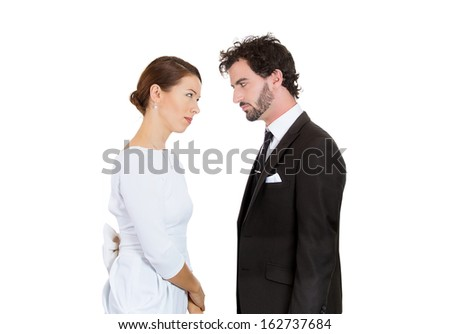 Closeup portrait of two people, man and woman, unhappy, angry couple staring at each other, blaming each other for the problem, isolated on white background. Marriage difficulties. Negative emotions - stock photo
