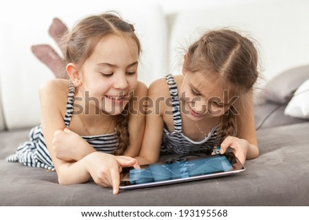 Closeup portrait of two smiling girls lying on couch and using tablet - stock photo