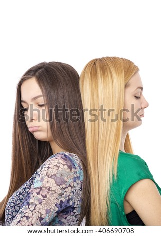 Closeup portrait of two sulky teenage girls standing back to back over white background - stock photo