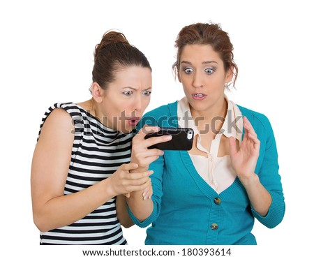 Closeup portrait of two women looking shocked upset while watching something on their cell phone, text message, sms, email isolated white background. Negative human emotions, facial expression feeling