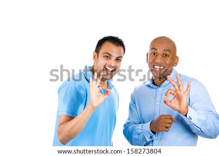 Closeup portrait of two young friendly men, happy coworkers; smiling, happy young business partners, students giving OK sign, isolated on white background with copy space. Corporate life, deal making - stock photo