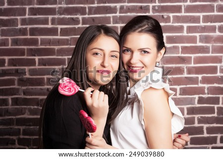 Closeup portrait of two young girlfriend girls with lollipops. Happy and cheerful teens. Red lips and hearts. Valentine's day concept. - stock photo